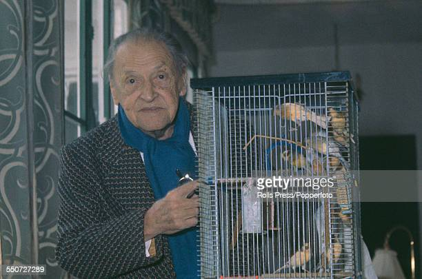 British playwright and novelist W Somerset Maugham pictured beside a birdcage containing various songbirds in January 1965