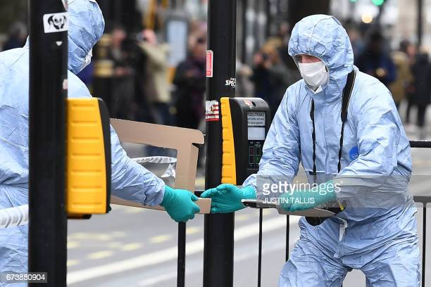 British police forensics officer passes a knife to a colleague as they collect evidence on Whitehall near the Houses of Parliament in central London...