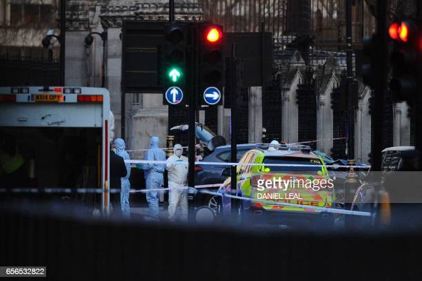 British police forensics officers work near a grey vehicle that crashed into the railings of the Houses of Parliament in Westminster central London...