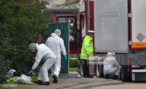 British Police forensics officers work on lorry found to be containing 39 dead bodies at Waterglade Industrial Park in Grays east of London on...