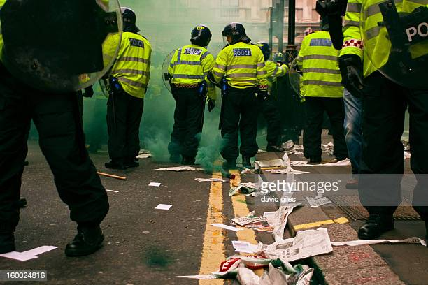 CONTENT] British police in riot gear stand with round riot shields as a green smoke bomb billows Debris from protestors lies on the floor