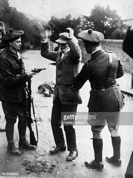 British police known as 'Black and Tans' for their mixandmatch military outfits of dark wool and khaki hold a suspected Sinn Fein member at gunpoint...