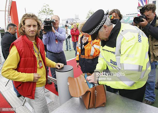 British police officer checks the bag of Jarno Trulli of Italy and Toyota at the entrance to the paddock as a part heightened security procedures...