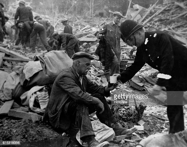 A British police officer hands a victim tea in the middle of the V2 bombing wreckage