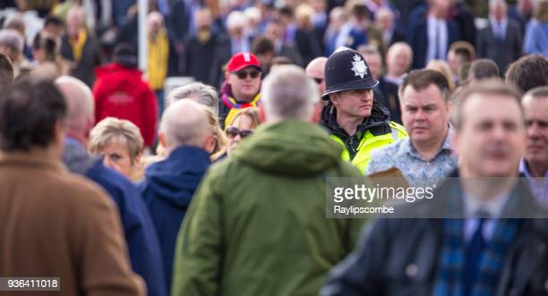 British police officer mingling with crowds of people on their way to the famous Cheltenham Festival in The Cotswolds.