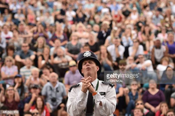 A British police officer reacts as he stands with spectators watching a giant screen showing the men's singles final match between Serbia's Novak...