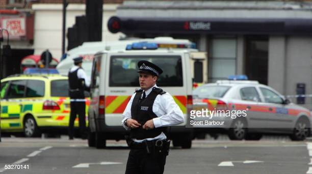 British police officer stands guard inside the police cordon outside of Stockwell Underground Station after a man was shot dead by armed officers on...