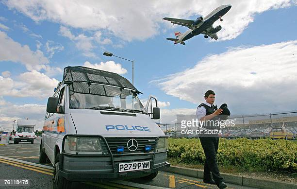 A British police officer walks beside a police van near Heathrow airport's Terminal 3 in west London 16 August 2007 Security has been increased...