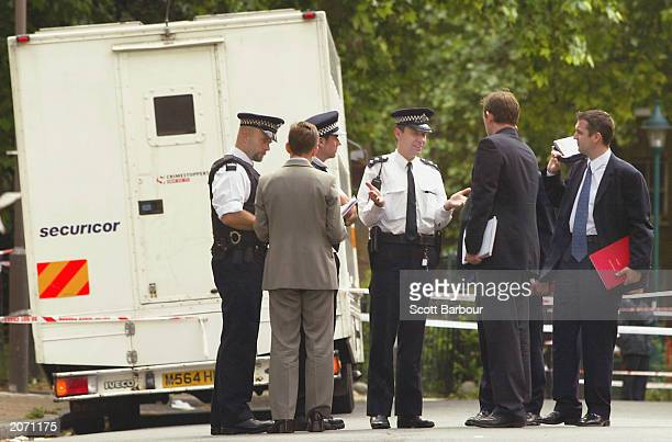 British police officers and inspectors talk in front of a security van which was hijacked as it arrived outside the Inner London crown Court on June...