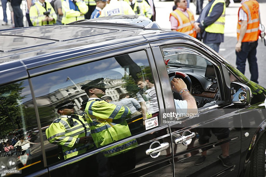 British police officers are seen reflected in the window of a London taxi cab during a protest against Uber Technologies Inc.'s car sharing service in London, U.K., on Wednesday, June 11, 2014. Traffic snarled in parts of Madrid and Paris today, with a total of more than 30,000 taxi and limo drivers from London to Berlin blocking tourist centers and shopping districts. Photographer: Simon Dawson/Bloomberg via Getty Images