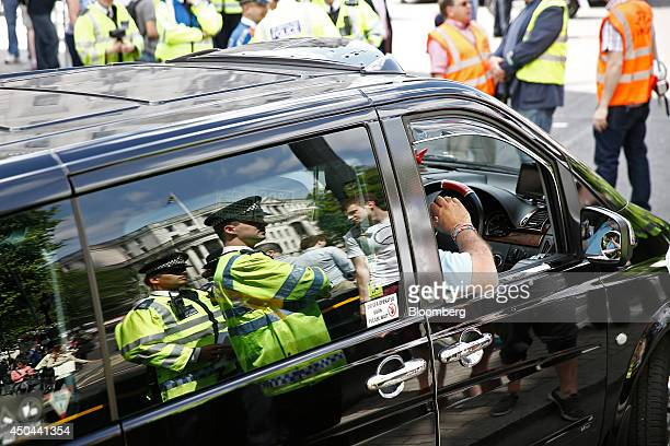 British police officers are seen reflected in the window of a London taxi cab during a protest against Uber Technologies Inc's car sharing service in...