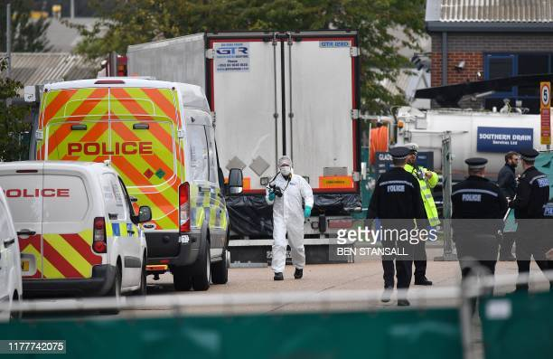 British Police officers in forsensic suits work near a lorry found to be containing 39 dead bodies as they work inside a police cordon at Waterglade...