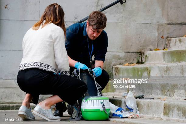 British police officers inspect items including a bag and a sheathed knife at the former parish church of St John's Smith Square in central London on...