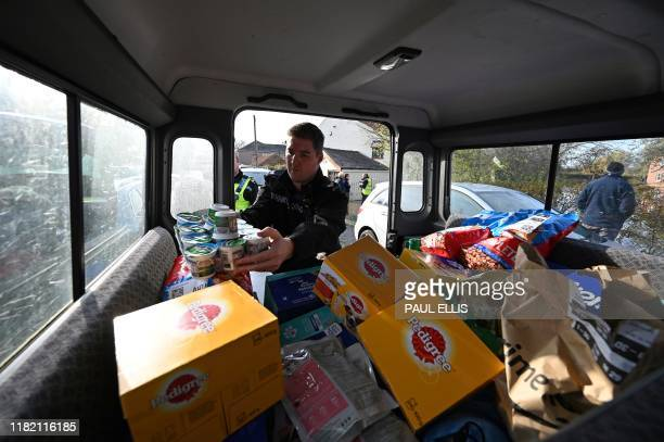 British police officers load donated food and provisions into the back of a Fire service Land Rover before distributing it to floodaffected residents...