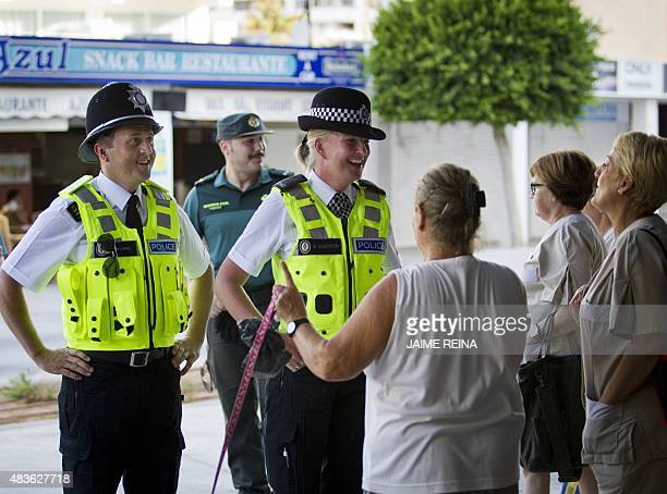 British police officers popularly known as 'bobbies' speak with some women as they patrol with Spanish Civil Guards at Punta Ballena street in the...