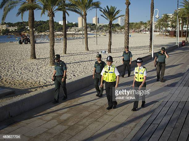 British police officers popularly known as 'bobbies' walk Spanish Civil Guards as they patrol at Punta Ballena street in the holiday resort of...