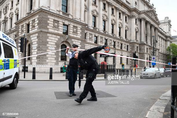 British police officers secure a cordon near the scene on Whitehall near the Houses of Parliament in central London on April 27 2017 where a man was...