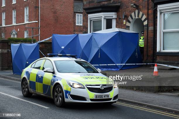 British Police officers stand by forensic tents outside a residential address in Stafford, central England on November 30 raided in connection with...