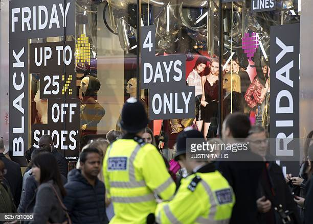 British police officers stand on duty as shoppers pass a promotional sign for 'Black Friday' sales discounts on Oxford Street in London on November...