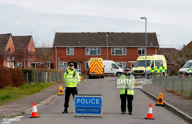 British police officers stand on duty at a cordon leading to a residential houseing estate as Military personnel in wearing protective coveralls work...