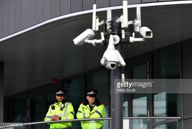 British Police officers stand on duty near CCTV cameras on the second day of the annual Conservative Party conference at the Manchester Central...