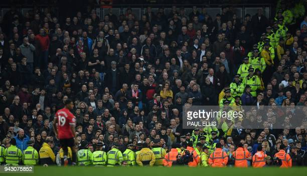 British police officers stand with stewards around the edge of the Manchester United supporter's area during the English Premier League football...
