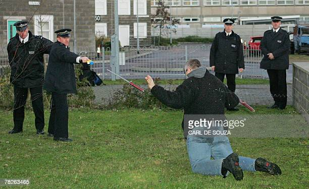 British police officers use a taser gun on a mock suspect armed with a knife during training at the Metropolitan Police Specialist Training Centre in...