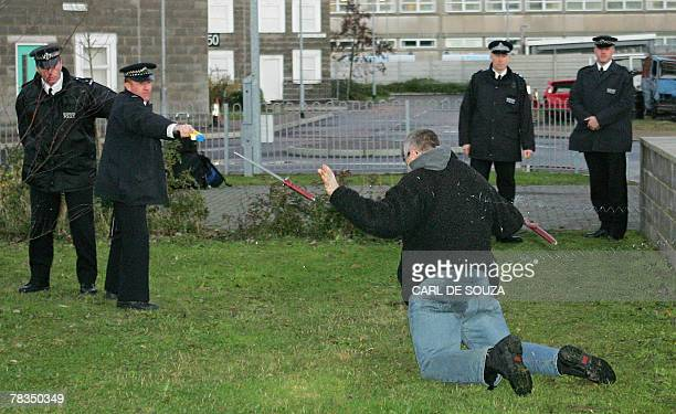 British police officers use a taser gun on a mock suspect armed with a knife during a training session at the Metropolitan Police Specialist Training...