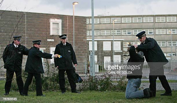 British police officers use a taser gun on a mock suspect during training at the Metropolitan Police Specialist Training Centre in Gravesend Kent in...