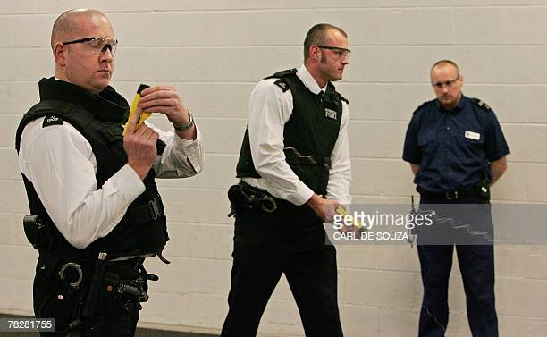 British police officers use taser guns at the Metropolitan Police Specialist Training Centre in Gravesend Kent 05 December 2007 Taser guns are to be...