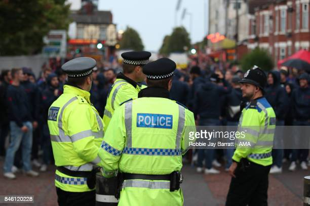 British Police Officers watch over fans of FC Basel prior to the UEFA Champions League match between Manchester United and FC Basel at Old Trafford...