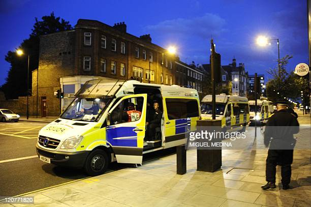 British police vans are parked along a street of Hackney in north London late on August 9 2011 Britain's worst riots in decades raged into on August...