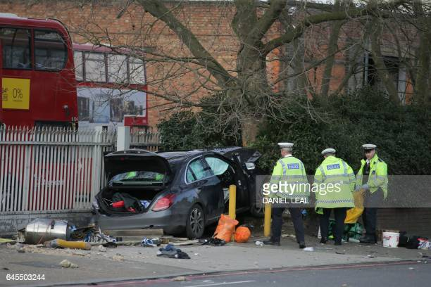 British police work at the scene where a car being driven along a main road collided with a wall and pedestrians in south London on February 26 2017...