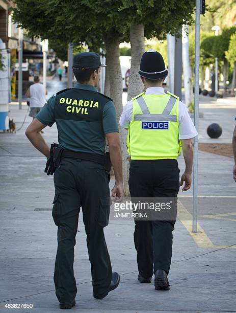 A British policeman popularly known as 'bobby' walks with a Spanish Civil Guard as they patrol at Punta Ballena street in the holiday resort of...