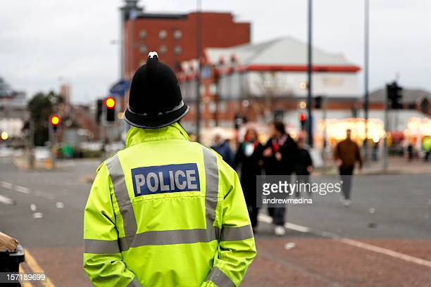 british policeman wearing tradtional  helmet observes people-see below for more - manchester uk stock photos and pictures