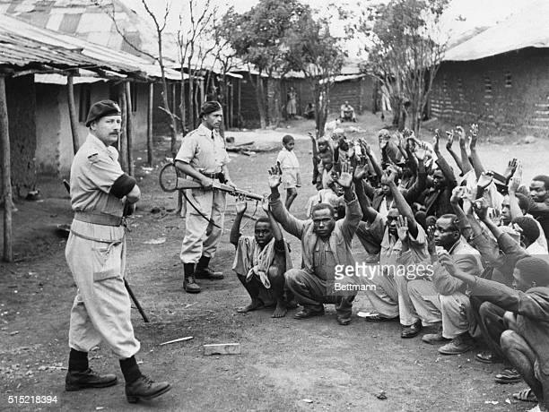British policemen hold men from the village of Kariobangi at gunpoint while their huts are searched for evidence that they participated in the Mau...