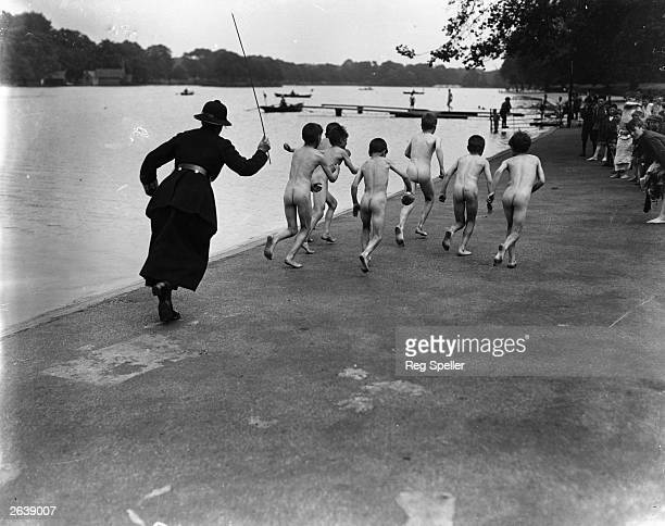 A British policewoman chasing after a group of naked street boys by the Serpentine in Hyde Park London