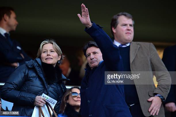 British politician and former champion athlete Sebastian Coe waves from the stands beside his wife Carole Annett as he arrives to attend the English...