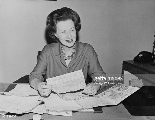 British politician Barbara Castle reads congratulatory telegrams at her desk at the Ministry of Transport in Southwark London on her first day of...