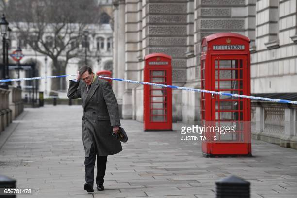 British politician Dominic Grieve lifts the police cordon as he walks along Whitehall in Westminster central London on March 23 2017 a day after a...