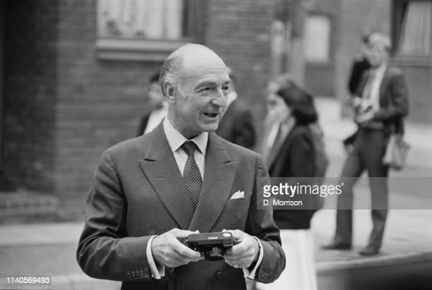 British politician John Profumo holding a camera at Toynbee Hall London UK 19th July 1984
