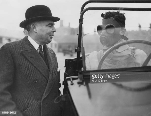 British politician Leslie Hore-Belisha , the Secretary of State for War, chats to a cadet driver in a gas mask during a visit to the Royal Military...