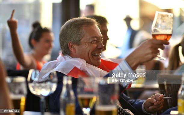 British politician Nigel Farage gestures with his glass at The Beer Factory Bar in Brussels on June 28 as he watches the Russia 2018 World Cup Group...