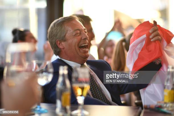 British politician Nigel Farage holds a flag of Saint George at The Beer Factory Bar in Brussels on June 28 as he watches the Russia 2018 World Cup...