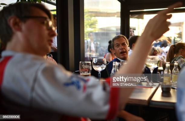British politician Nigel Farage looks towards an England football fan at The Beer Factory Bar in Brussels on June 28 as he watches the Russia 2018...