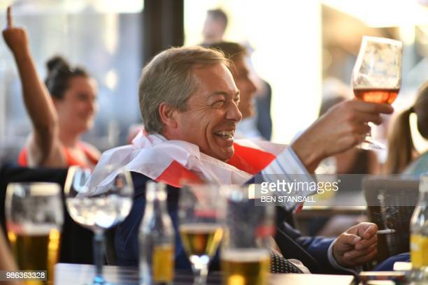 British politician Nigel Farage wears a flag of Saint George around his shoulders as he drinks at The Beer Factory Bar in Brussels on June 28 as he...