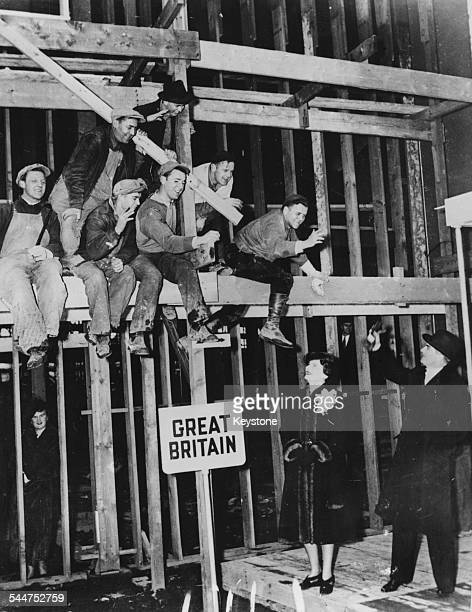 British politician Sir Anthony Eden and his wife waving up at a group of workmen at work on the British site for the New York World's Fair December...