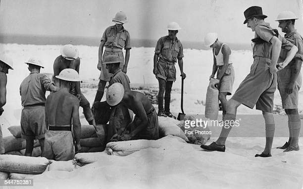 British politician Sir Anthony Eden watching a sandbagging party at work on a visit to Palestine November 11th 1940
