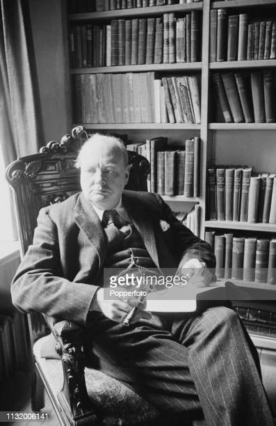 British politician Winston Churchill pictured seated with a book and cigar in the library of Chartwell country house near Westerham in Kent England...