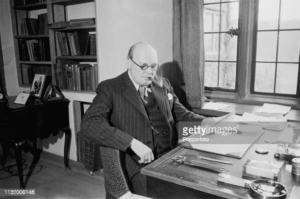 British politician Winston Churchill pictured seated with a cigar at a desk in the library of Chartwell country house near Westerham in Kent England...